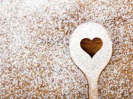 Heart hole spoon on the wooden pastry board - baking background Stock Photo