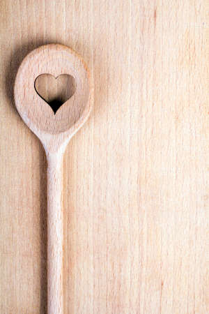 wooden spoon: Heart hole spoon on the wooden pastry board - baking background Stock Photo