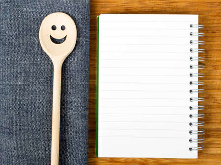 blank notebook and wooden spoon on the table background photo