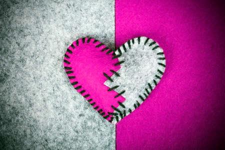 corazon roto: cosido roto sent�a el coraz�n en un sobre un fondo de dos colores Foto de archivo