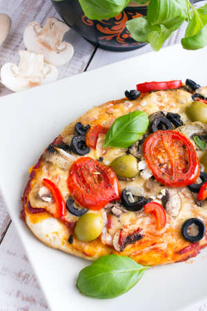 pizza with tomatoes mushrooms olives and peppers served on a plate on a wooden table
