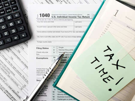 tributos: Cierre de formulario de impuestos de US Individual 1040 con la calculadora y la pluma.