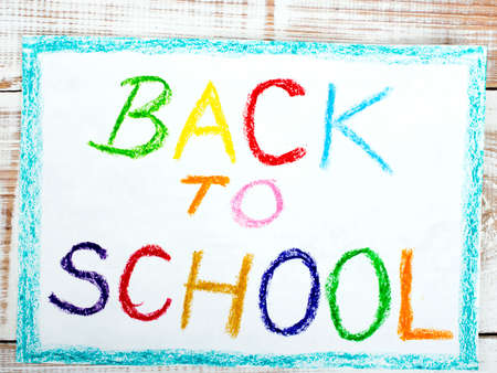 kids painting: words BACK TO SCHOOL written in blue crayon on paper Stock Photo