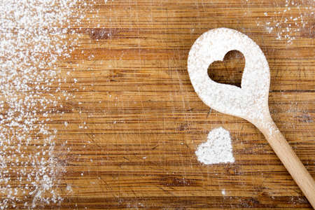 Heart hole on the wooden spoon pastry board - baking background Banque d'images