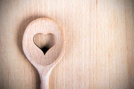 Heart hole on the wooden spoon pastry board - baking background Stock Photo