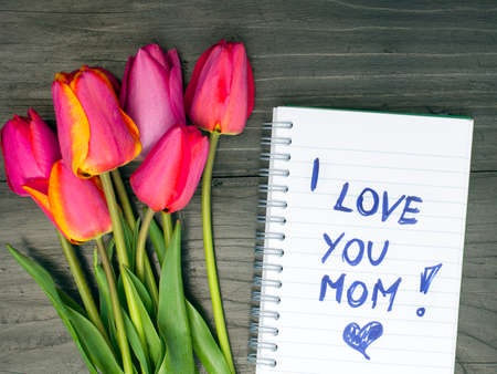 note pad: tulip bouquet and notepad with words I love you mom Stock Photo