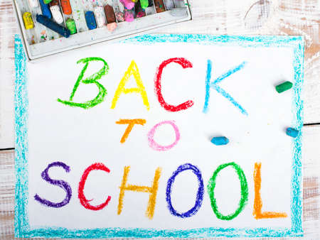 school picture: words BACK TO SCHOOL written in blue crayon on paper Stock Photo