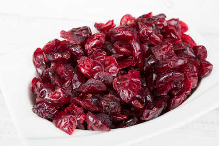 Dried cranberries in a bowl on a white background Stock Photo