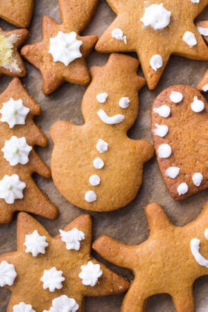 gingerbread cookies: Colorful Christmas gingerbread cookies on  baking paper Stock Photo