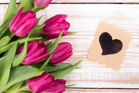 vintage card: A bouquet of tulips and ornamental card with heart on a wooden background