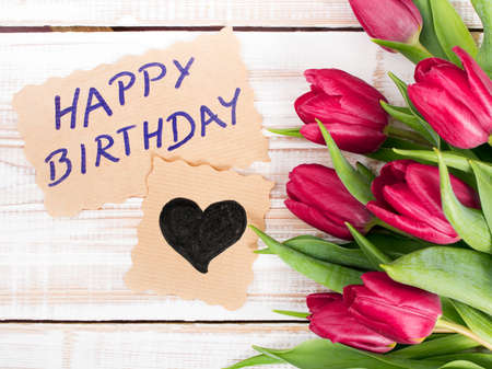 birthday presents: Birthday card and tulip bouquet on white wooden background