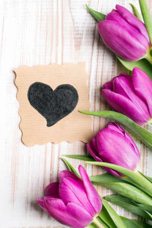 pink vintage background: A bouquet of tulips and ornamental card with heart on a wooden background