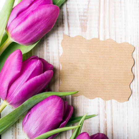 vintage card: A bouquet of tulips and an empty paper card on wooden background Stock Photo