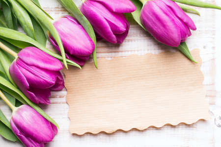 A bouquet of tulips and an empty paper card on wooden background Standard-Bild