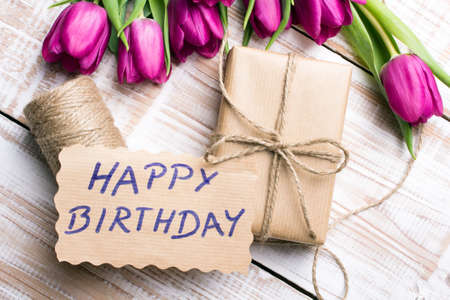 Birthday card and tulip bouquet on white wooden background