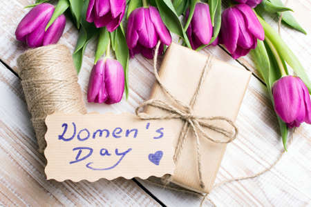 Women's day card and a bouquet of beautiful tulips on wooden background Standard-Bild