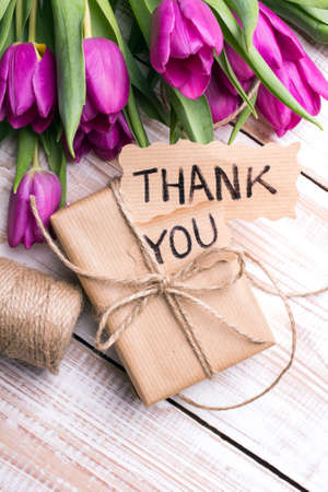 Thank you card, gift box and tulip bouquet on white wooden background