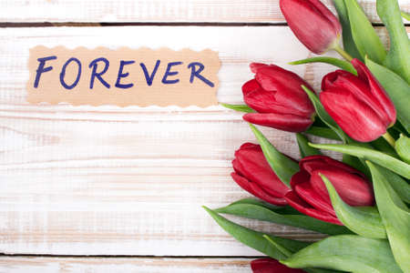 forever: word FOREVER and bouquet of tulips on wooden background Stock Photo