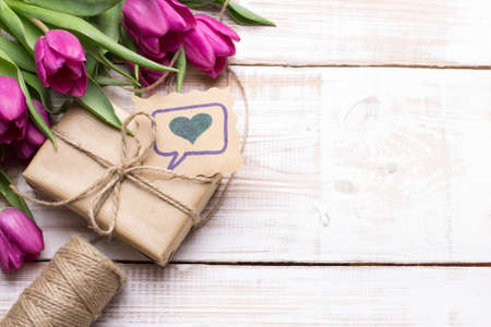 wooden background: Gift box and tulips bouquet on white wooden background - retro style
