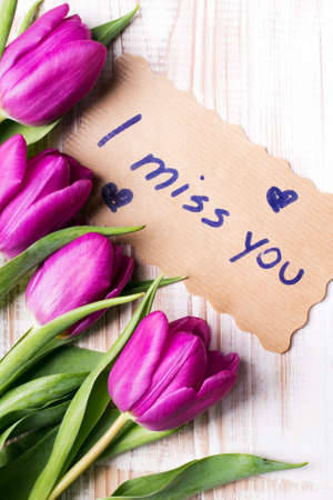 i miss you: words I MISS YOU and bouquet of tulips on wooden background