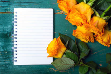 parer: bouquet of orange roses and blank notebook  on green wodden background Stock Photo