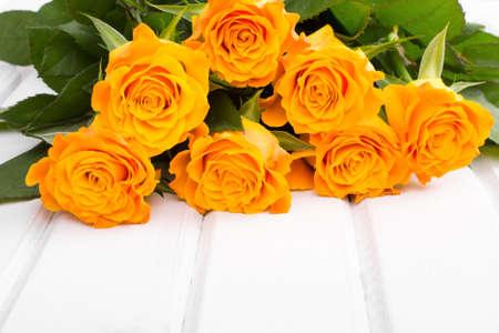 rosas naranjas: ramo de rosas de color naranja sobre un fondo de madera blanca
