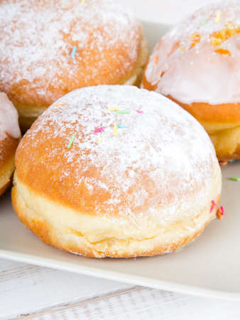 frosting': donuts with frosting and powdered sugar on a platter