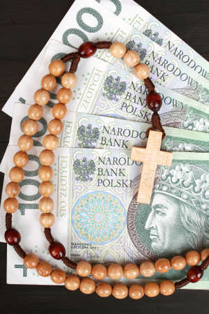 Closeup of a wooden rosary on Polish banknotes