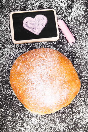 donut with powdered sugar and heart drawing