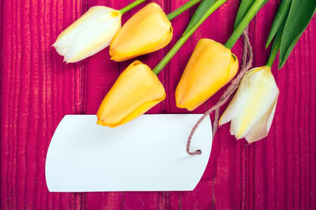 yellow notepad: yellow tulip bouquet and blank card on pink wooden tray