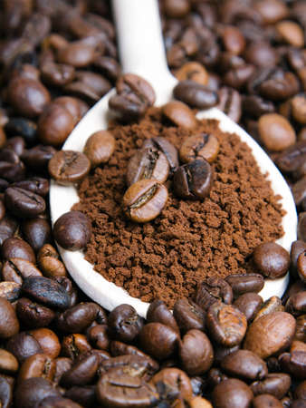 instant coffee in spoon on coffee beans background