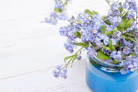 small blue flowers in a jar on a white wooden background