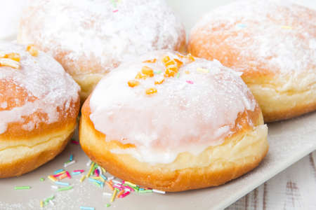 donuts with frosting and powdered sugar on a platter