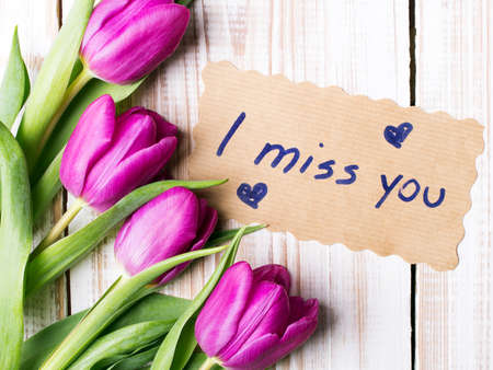 words I MISS YOU and bouquet of tulips on wooden background