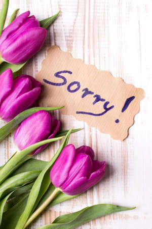 word SORRY and bouquet of tulips on wooden background