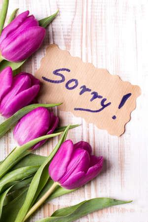 Wort SORRY und Strauß Tulpen auf Holzuntergrund Standard-Bild - 71429183