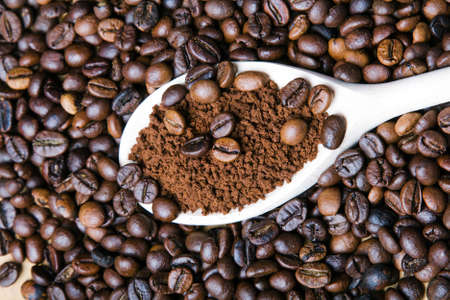 Iinstant coffee in spoon on coffee beans background