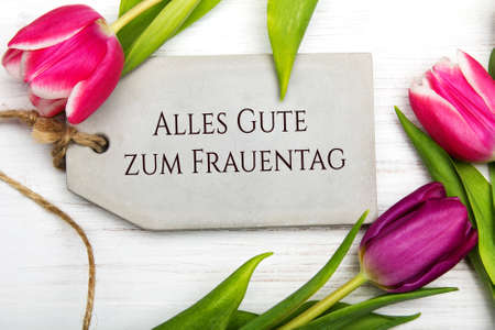 Women's day card with German words 'Alles gute zum frauentag' - All the best for women's day.Tulip flower and small heart on white wooden background.