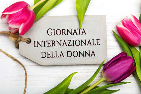 Womens day card with Italian words Giornata internazionale della donna. Tulip flower and small heart on white wooden background