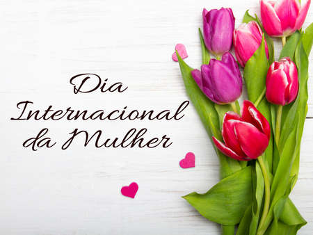 Women's day card with Portuguese words' Dia Internacional da Mulher'.Tulip flower and small wooden heart on white background Standard-Bild