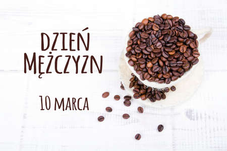 Mens day card with Polish words  DZIEŃ MĘŻCZYZN and  coffee beans cup on white wooden background Stock Photo