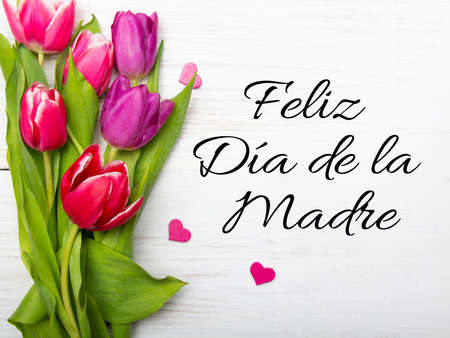 Mothers day card with Spanish worsd: Happy mothers day, andtulip bouquet on white wooden background