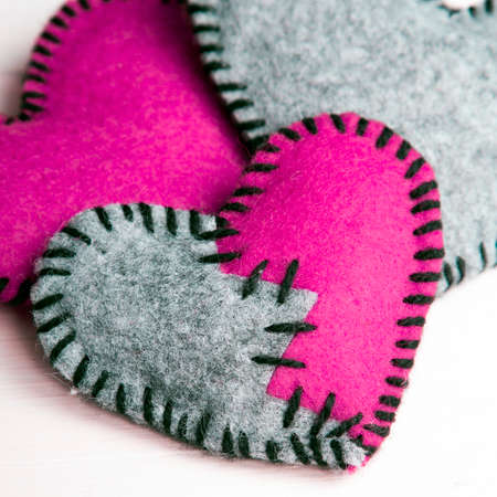 background texture metaphor: Three felt hearts on a white wooden background, valentines composition Stock Photo