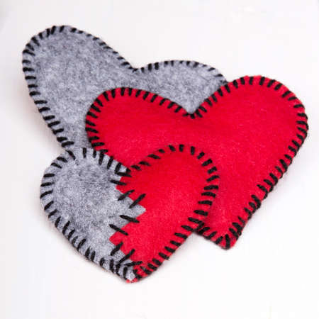 Three felt hearts on a white wooden background, valentines composition Stock Photo