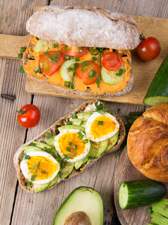 Sandwiches with avocado, eggs and tomato on a wooden background. Fresh organic vegetables, eggs and whole wheat bread. Healthy breakfast. Retro style. Stock Photo