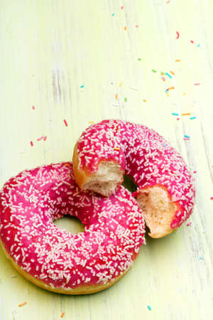 tasty donuts with icing and chocolate on green wooden background, copy space