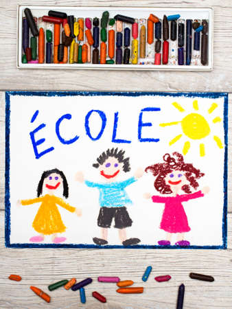 Photo of colorful drawing: French word SCHOOL and happy children. First day at school.