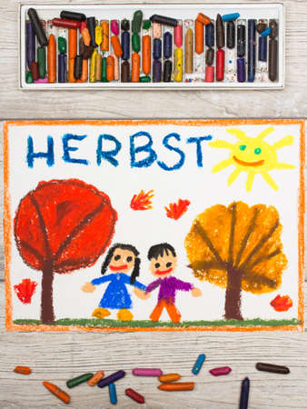 Photo of  colorful drawing: German word Autumn, trees with red and orange leaves and smiling people,