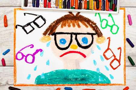 Photo of colorful drawing: Sad and crying boy with his grasses. Defect of vision.