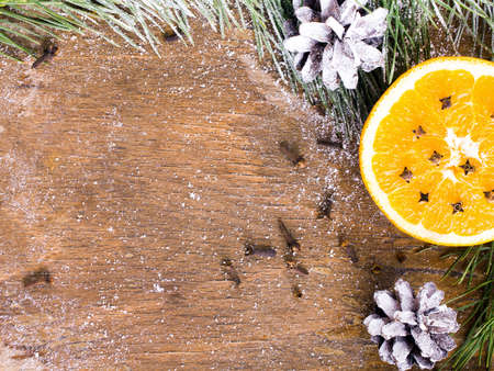 Christmas background with orange, cloves, stars and fir branches on wooden background